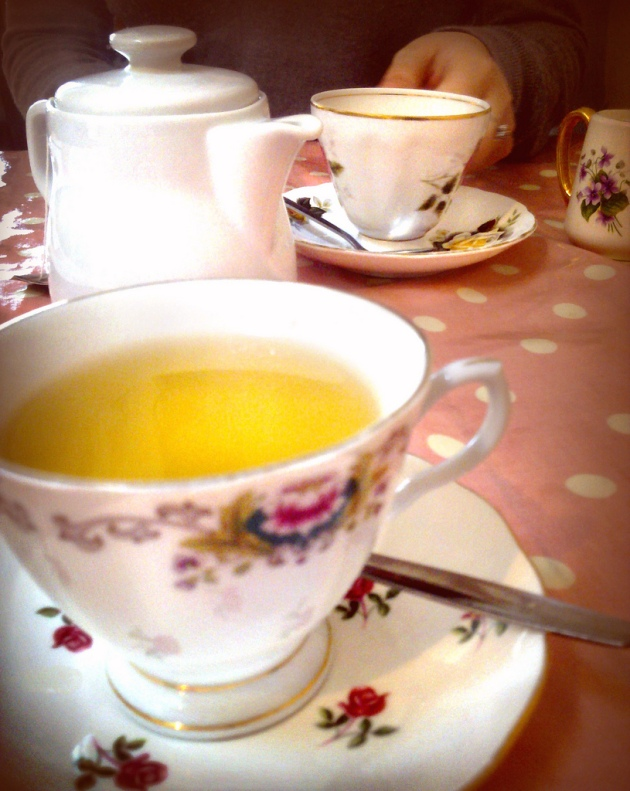breakfast, jasmine tea in a floral tea cup on a pink and white polka dot table cloth, with a teapot behind