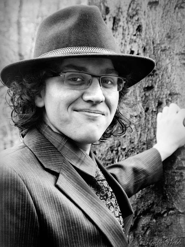 A black and white portrait of Dayal with his hand on a tree, taken in the woods in autumn.