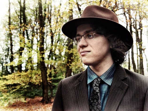 A contrast portrait of Dayal standing in the woods wearing a hat, taken in autumn.