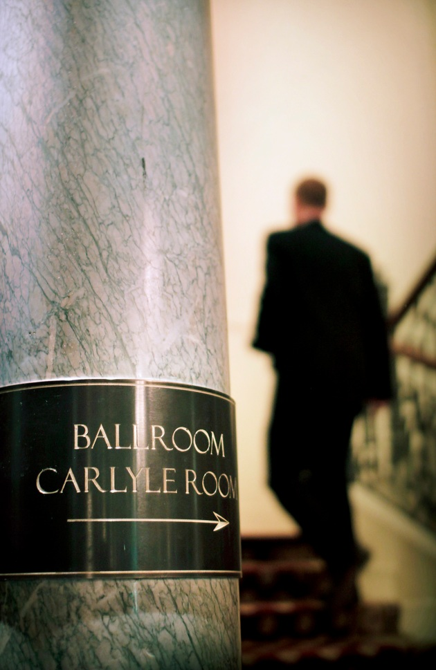 Ballroom and Carlyle Room sign at the Mandarin Oriental Hotel in Knightsbridge, with a silhouetted figure walking upstairs behind