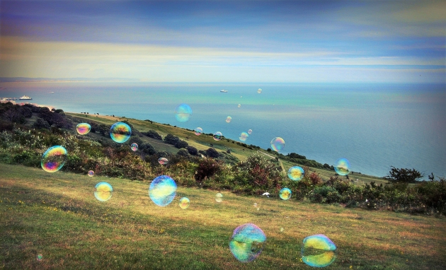 Bubbles floating over Beachy Head downs overlooking Eastbourne and the sea
