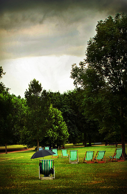 Man sitting in a Green Park deckchair with an umbrella under rainclouds