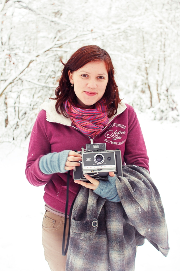 Becky in snowy woods holding poloroid camera