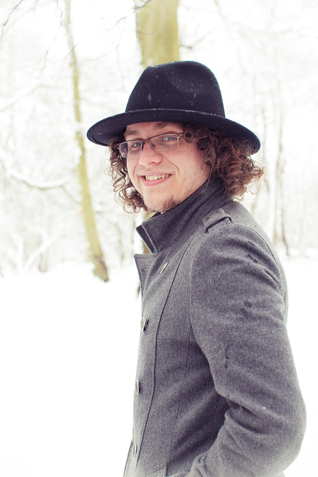 Dayal in snowy woods wearing a fedora