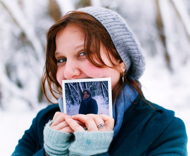 Standing in snowy woods with poloroid photo of myself