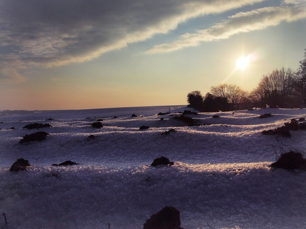Sun setting over a snowy field in the winter near Amersham